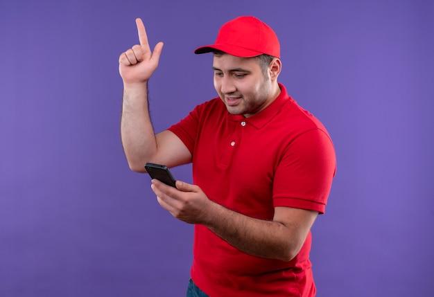 Молодой курьер в красной униформе и кепке смотрит на экран смартфона, указывая пальцем вверх, имея новую отличную идею, стоящую над фиолетовой стеной