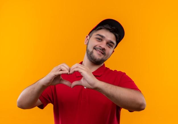 빨간 제복을 입은 젊은 배달 남자와 가슴 웃고있는 손가락으로 심장 제스처를 만드는 모자
