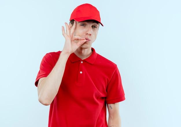 빨간 제복을 입은 젊은 배달 남자와 흰 벽 위에 서있는 지퍼로 입을 닫는 것처럼 침묵 제스처를 만드는 모자