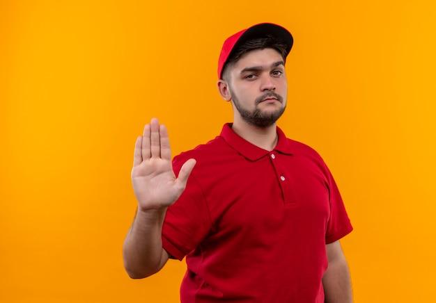Молодой курьер в красной форме и кепке делает знак остановки рукой, смотрящей с серьезным лицом