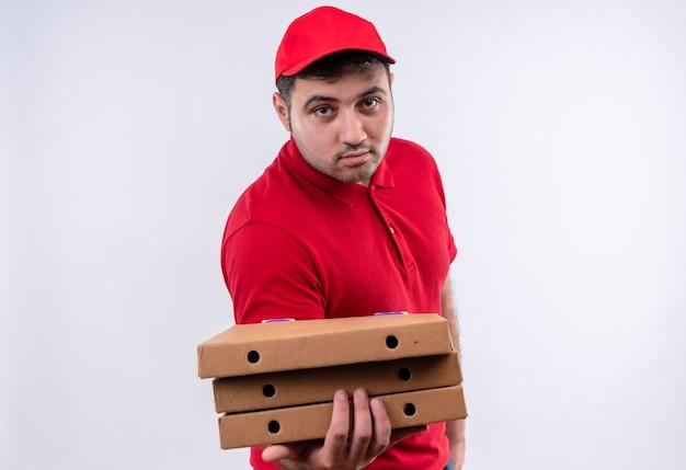 빨간 제복을 입은 젊은 배달 남자와 흰 벽 위에 서있는 얼굴에 자신감이있는 미소로 피자 상자를 제공하는 모자