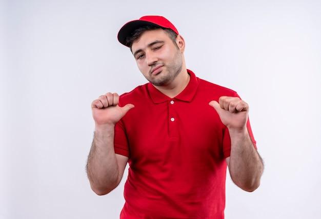 Молодой курьер в красной форме и кепке, указывая пальцами на себя, самодовольный и гордый стоит у белой стены