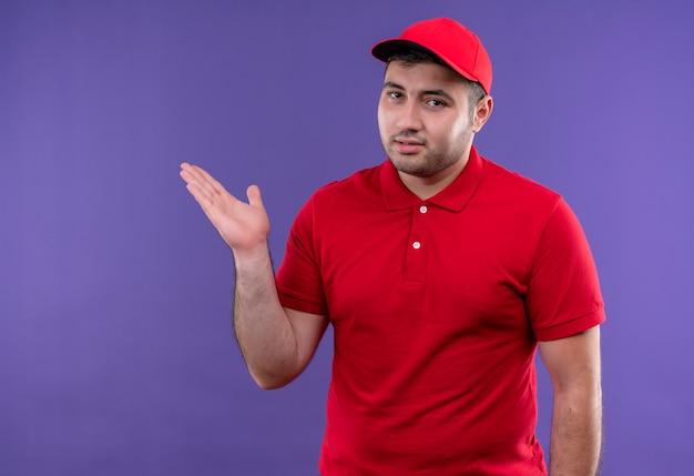 빨간 제복을 입은 젊은 배달 남자와 보라색 벽 위에 서있는 그의 손의 팔로 복사 공간을 제시하는 모자