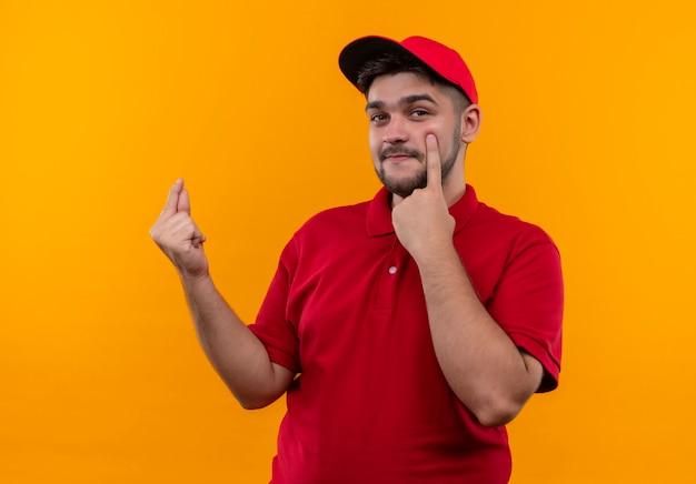 빨간 제복을 입은 젊은 배달 남자와 돈을 요구하는 그의 눈을 가리키는 손가락을 문지르는 모자