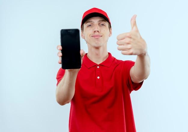 Молодой курьер в красной форме и кепке показывает смартфон, уверенно улыбаясь, показывает палец вверх, стоя над белой стеной