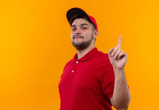 빨간 유니폼과 모자에 젊은 배달 남자 자신감 보여주는 검지 손가락 미소