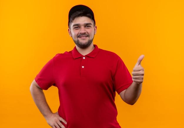 Молодой курьер в красной форме и кепке, уверенно улыбаясь, показывает палец вверх