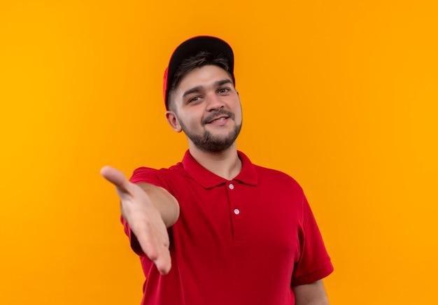 빨간 제복을 입은 젊은 배달 남자와 손을 제공하는 친절한 인사 웃는 모자