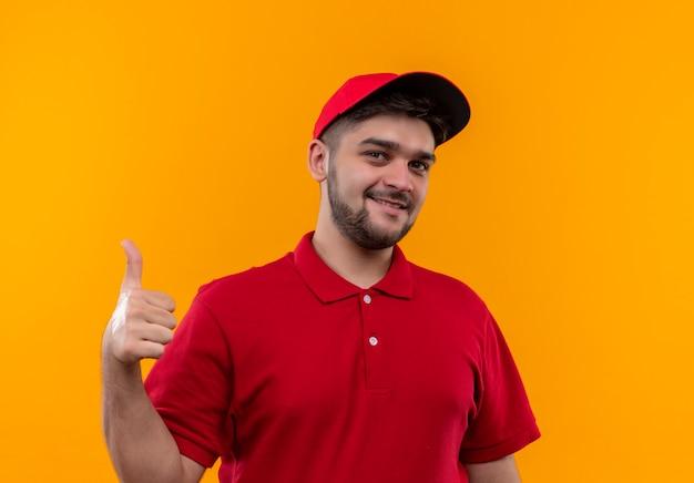 Молодой курьер в красной форме и кепке дружелюбно улыбается, показывает палец вверх