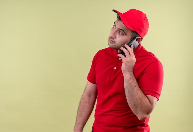 빨간 제복을 입은 젊은 배달 남자와 녹색 벽 위에 서있는 심각한 얼굴로 제쳐두고 찾고 휴대 전화에 얘기하는 모자