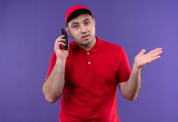 빨간 제복을 입은 젊은 배달 남자와 보라색 벽 위에 서있는 어깨를 으쓱하는 혼란스러워 보이는 휴대 전화 통화 모자