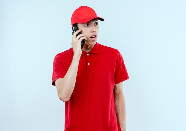 Молодой курьер в красной форме и кепке разговаривает по мобильному телефону, выглядит удивленным и удивленным, стоя у белой стены
