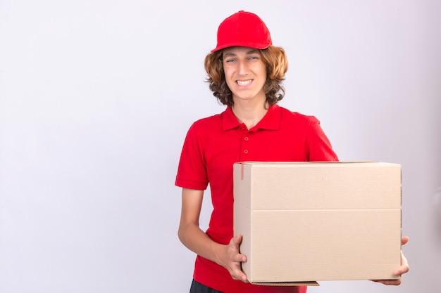 孤立した白い背景の上に元気に立って笑顔のカメラを見て大きな段ボール箱を保持している赤い制服を着た若い配達人