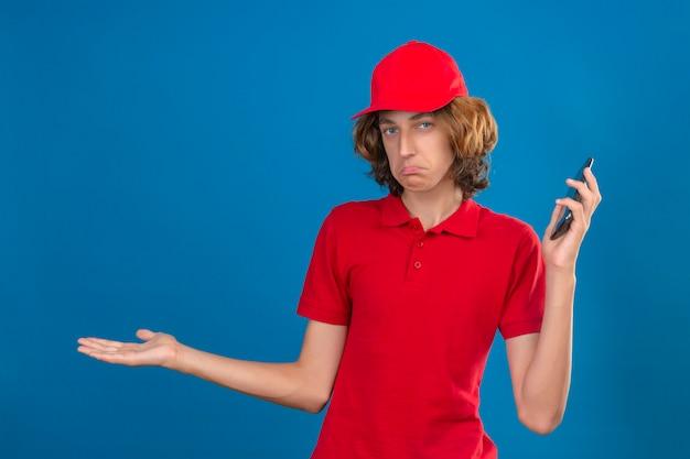 無知な手で携帯電話を手に保持している赤い制服を着た若い配達人と開いた腕と混同しない分離の青い背景の上に立っている考え概念