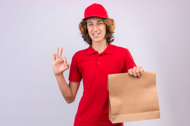 격리 된 흰색 배경 위에 유쾌 하 게 웃 고 확인 서명 하 고 종이 패키지를 들고 빨간 제복을 입은 젊은 배달 남자