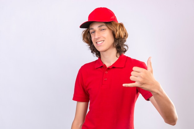 赤い制服を着た若い配達人が私に孤立した白い背景に自信を持って探しているジェスチャーを呼び出す