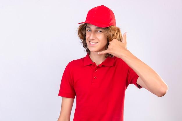 赤い制服を着た若い配達人が分離の白い背景の上に元気に笑みを浮かべて自信を持って探しているジェスチャーを呼び出す