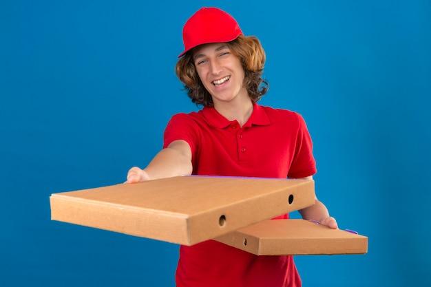 孤立した青い背景にフレンドリーな立っている笑顔のピザの箱を伸ばして赤い制服を着た若い配達人