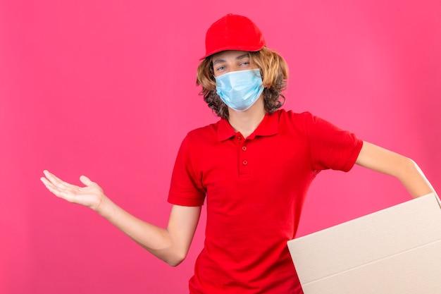 Молодой курьер в красной форме, носящий медицинскую маску, держит картонную коробку, улыбаясь веселым представлением и указывая ладонью, глядя в камеру на изолированном розовом фоне