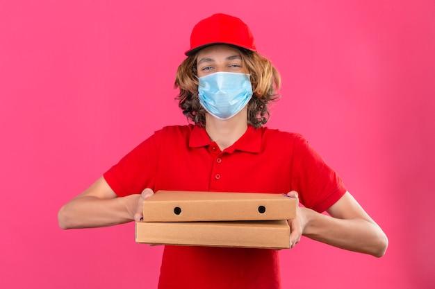 Молодой курьер в красной форме в медицинской маске держит коробки для пиццы, глядя в камеру, дружелюбно улыбаясь с счастливым лицом на изолированном розовом фоне