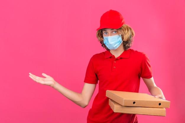 Молодой курьер в красной форме, носящий медицинскую маску, держит коробки для пиццы, улыбаясь веселым представлением и указывая ладонью, глядя в камеру на изолированном розовом фоне