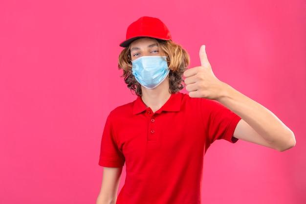 Молодой курьер в красной форме в медицинской маске, глядя в камеру, весело улыбаясь, показывая большой палец вверх на изолированном розовом фоне