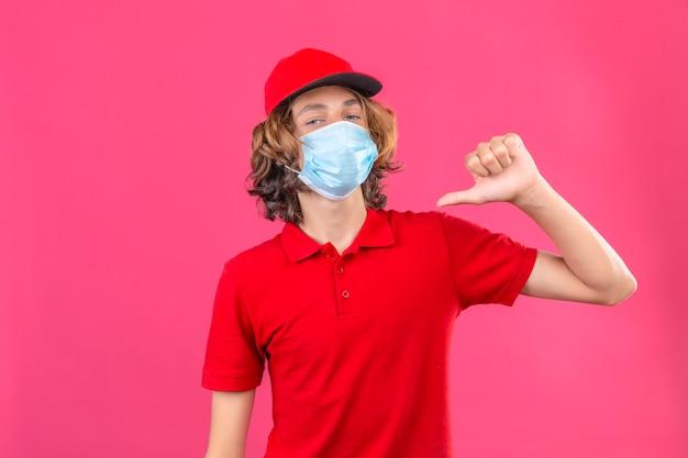 Молодой курьер в красной форме, одетый в медицинскую маску, выглядит уверенно, указывая на себя на изолированном розовом фоне