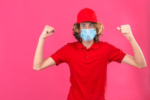 Молодой курьер в красной форме в медицинской маске, поднимающий кулаки, гордый и уверенный победитель, стоящий на изолированном розовом фоне