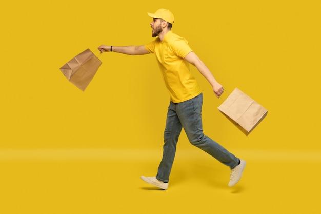 Молодой курьер в желтой форме работает с изолированными бумажными пакетами