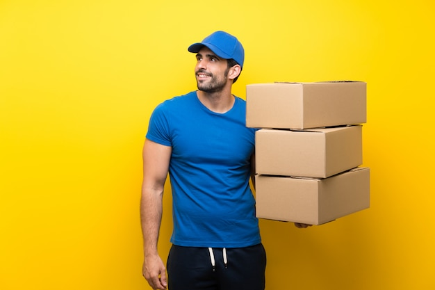 Young delivery man over isolated yellow wall looking up while smiling