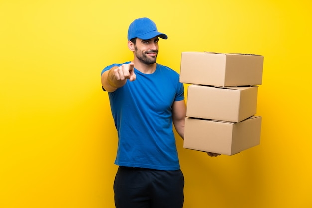 Young delivery man over isolated yellow wall points finger at you with a confident expression