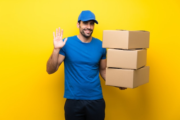 Young delivery man over isolated yellow wall saluting with hand with happy expression
