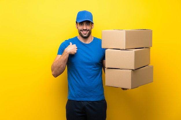 Young delivery man over isolated yellow wall with surprise facial expression