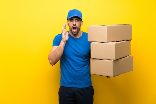 Young delivery man over isolated yellow wall with surprise and shocked facial expression