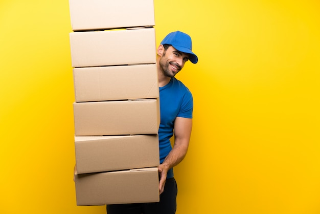 Young delivery man over isolated yellow wall