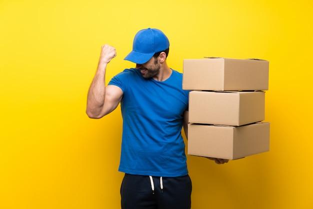 Молодой работник доставляющий покупки на дом над изолированной желтой стеной празднуя победу