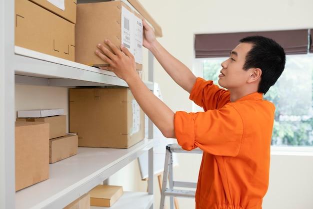 Giovane uomo di consegna che prepara i pacchi per la consegna