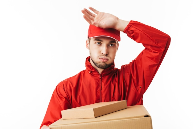 Young delivery man in red cap and jacket holding boxes in hands tiredly