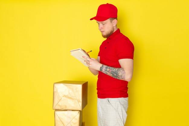 Young delivery man in red polo red cap white jeans writing down on yellow repartidor