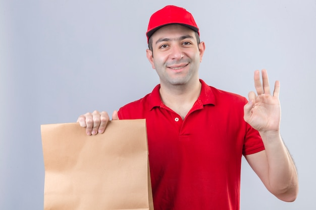 Young delivery man in red polo shirt and cap holding paper package smiling friendly doing ok sign over isolated white wall
