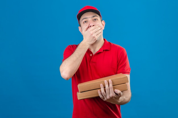 Giovane fattorino in scatole di pizza della tenuta della camicia e del cappuccio di polo rosso che coprono bocca di mano scioccata che controlla parete blu isolata