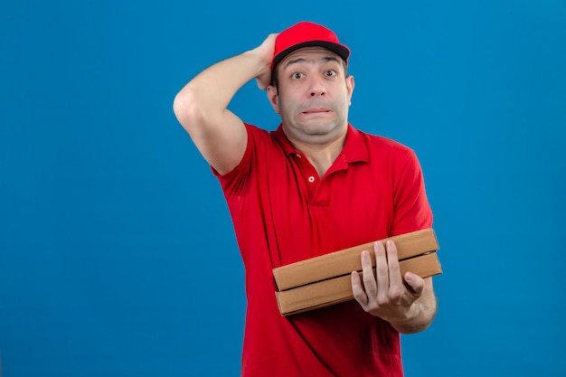 Young delivery man in red polo shirt and cap holding pizza boxes frustrated with hand on head for mistake over isolated blue wall