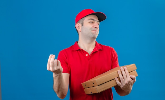 Young delivery man in red polo shirt and cap holding pizza boxes making delicious italian gesture with hand smiling over isolated blue wall