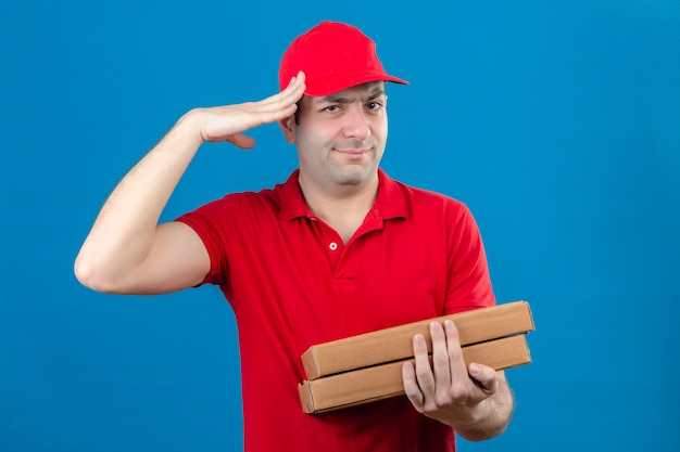 Young delivery man in red polo shirt and cap holding pizza boxes making salute ready for work standing with serious face over isolated orange wall