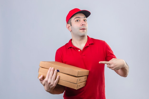 Young delivery man in red polo shirt and cap holding pizza boxes pointing with finger looking confident over isolated white wall