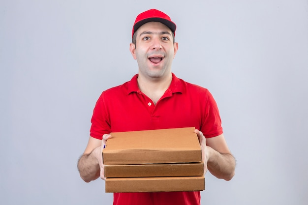 Young delivery man in red polo shirt and cap holding pizza boxes smiling cheerfully standing over isolated white wall