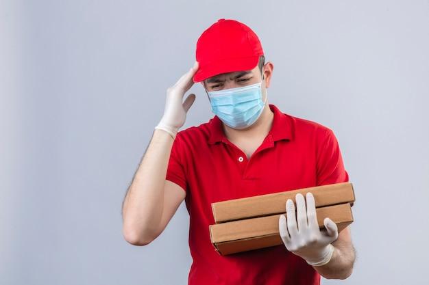 Giovane fattorino in camicia e cappuccio di polo rossi in scatole mediche della pizza della tenuta della maschera che sembrano indisposte commoventi della testa che soffrono dall'emicrania sopra la parete bianca isolata