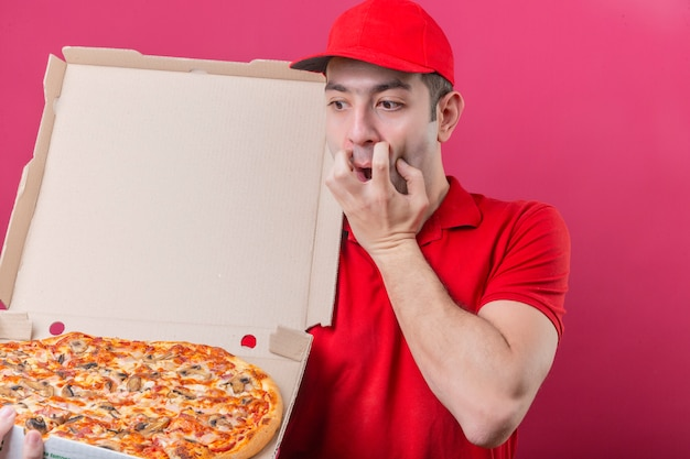 Young delivery man in red polo shirt and cap standing with box of fresh pizza looking at it shocked frightened over isolated pink background