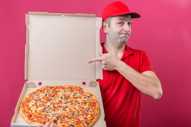 Young delivery man in red polo shirt and cap standing with box of fresh pizza pointing to it with finger looking at camera convinced and confident over isolated pink background