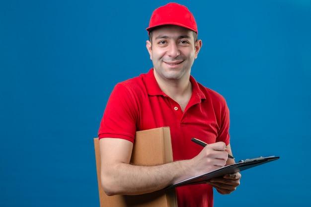 Giovane uomo di consegna in maglietta polo rossa e cappuccio in piedi con appunti e penna tenendo la scatola della pizza guardando la fotocamera con il sorriso sul viso isolato su sfondo blu